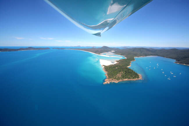 Hill inlet reflects off the aircraft wing.